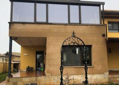 Cerramiento de aluminio en una terraza abierta, con cristales de seguridad, bajo emisivos, carpintería de aluminio color marrón con bajante incluida