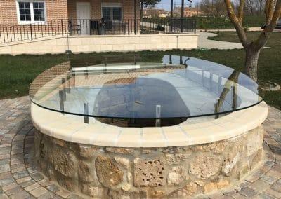 Vidrio de seguridad para proteger la boca de un pozo en un patio.