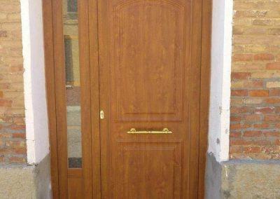 Puerta Exterior Aluminio de seguridad tipo Clásica color Roble con tirador dorado en Mazariegos (Palencia)