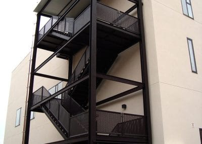 Escalera exterior de emergencia fabricada en hierro, con barandilla de chapa perforada en Palencia