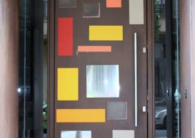 Puerta exterior en chapa corten con vidrios decorativos de diferentes colores tienda de Valladolid