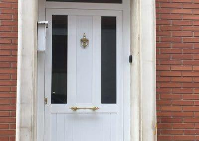 Puerta Exterior con panel clásico en color blanco con tirador y golpeador dorado en Palencia