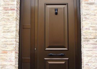 Puerta Exterior con panel clásico en color bronce con tirador y golpeador color forja en Palencia