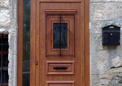 Puerta Exterior con panel rústico imitación madera, con reja y roseta imitación forja en Palencia.